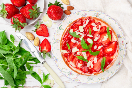 Homemade delicious strawberry tart with custard or whipped cream, with mint leaves and almond petals in a plate on a white wooden table. Dessert for gourmets. Selective focus