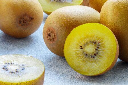 Golden (yellow) organic kiwi. Whole and cut ripe juicy fruits on grey background. kiwifruit.  Actinidia chinensis. Selective focus