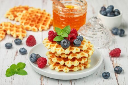 Viennese crispy waffles with fresh berries (raspberries and blueberries) with honey and mint leaves on a white plate on the table. Delicious homemade summer gourmet Breakfast. Rustic style. Selective focus Banco de Imagens