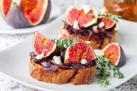 Sandwichs baguette aux céréales aux figues, fromage feta, marmelade d'oignons rouges et thym . Snack délicieux pour les gourmands. Mise au point sélective Banque d'images