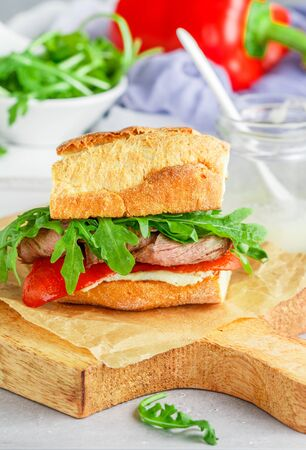 Delicatessen sandwich with beef, baked red bell peppers, arugula and horseradish sauce