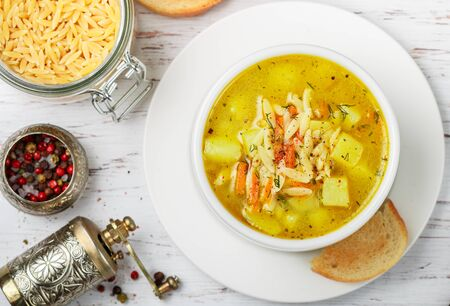 Chicken soup with potatoes, carrots and pasta Orzo in a white plate on a wooden table. Minestrone. Mediterranean (Italian) cuisine. Selective focus