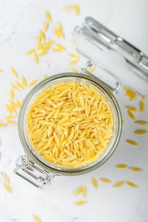 Orzo, a form of pasta shaped like rice in a glass jar on a marble surface. Selective focus Фото со стока
