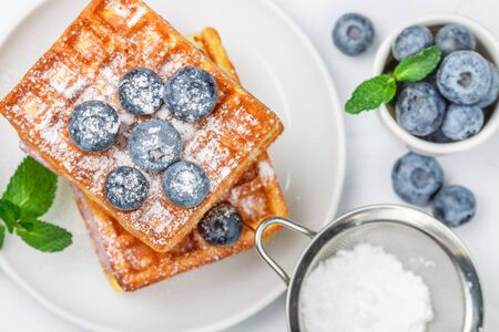 Traditional homemade Belgian (Viennese) waffles with fresh berries (blueberries) and powdered sugar. Delicious breakfast. Selective focus, top view Фото со стока