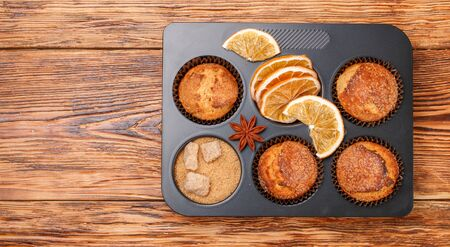Fresh baked homemade citrus (orange, Mandarin) cakes muffins with brown sugar, cinnamon and star anise in black teflon baking dish over on wooden table. Selective focus, Top view