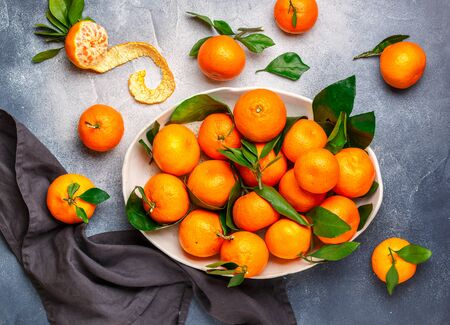 Fresh citrus mandarin oranges fruit (tangerines, clementines,) with leaves in a light dish on a gray stone or concrete background. Selective focus, top view and copy space Фото со стока