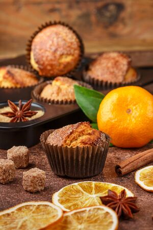 Fresh baked homemade citrus (orange, Mandarin) cakes muffins with brown sugar, cinnamon and star anise in black teflon baking dish over on wooden table. Selective focus
