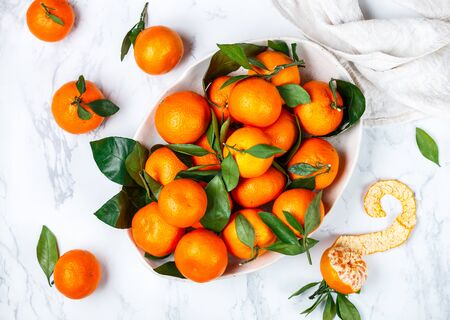Fresh organic citrus mandarin oranges fruit (tangerines, clementines) with leaves in a light dish on a marble background. Selective focus, top view and copy space Stock Photo