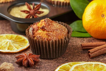 Fresh baked homemade citrus (orange, Mandarin) cakes muffins with brown sugar, cinnamon and star anise on wooden table close up. Selective focus Фото со стока