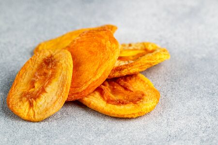 Dried delicious peaches on a gray concrete or stone background. An ingredient for making sweet dishes. Useful fruit. Healthy snack. Selective focus, copy space