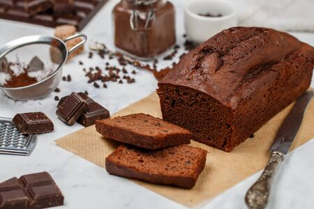 Sliced homemade chocolate banana pound cake loaf. Delicious dessert for Breakfast. A treat for tea. Ingredients on a light wooden table. Selective focus