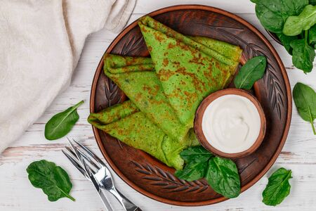 Spinach green pancakes (crepes) with sour cream. Delicious healthy Breakfast in a clay plate on a light wooden background. Selective focus, top view