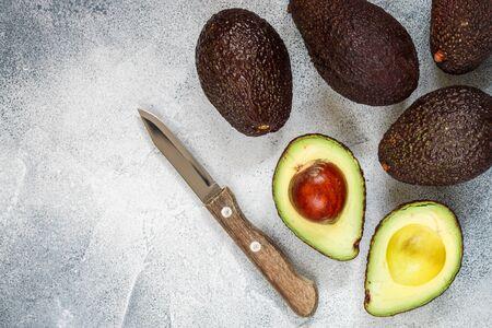 Całe i pokrojone w pół dojrzałe organiczne awokado i nóż na szaro