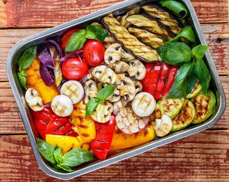 Légumes frais grillés - poivrons rouges et jaunes, oignons violets, tomates, ail, aubergines, courgettes et champignons champignons. Servi avec du basilic. Mise au point sélective, vue de dessus