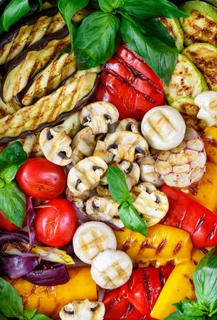 Grilled fresh vegetables - red and yellow bell peppers, purple onions, tomatoes, garlic, eggplants, zucchini and mushrooms champignons. Served with Basil. Selective focus, top view