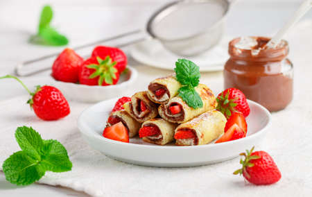 Rolls with chocolate and nut filling, fresh strawberry berries, powdered sugar and mint. Foto de archivo