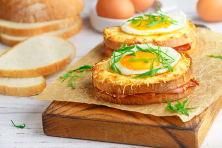 Sandwich white bread with ham or bacon, mustard, cheese, Bechamel sauce, watercress and eggs. CROQUE MADAME. traditional French cuisine. Selective focus 免版税图像
