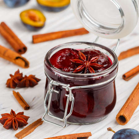 Jar with homemade plum jam with cinnamon and star anise on a white wooden background. Fresh fruit with spices on the table. Selective focus, square image