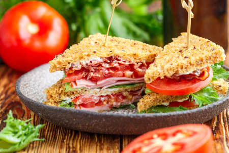 Delicious club sandwiches with green salad lettuce, ham, bacon, fresh tomatoes and sauce. Lunch concept. Selective focus