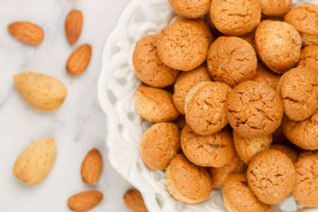 Amaretti-traditional Italian almond cookies in a white plate on a marble top view background. Amarettini biscuits close-up. Selective focus