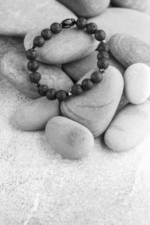 Beautiful bracelet made of natural black volcanic lava. Jewelry made of round-shaped beads is placed on large sea stones. Selective focus, copy space Standard-Bild