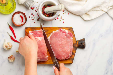 Pork. Fresh raw meat on a chopping board, salt, pepper in a mortar, garlic, olive oil and red chili pepper on a marble background. A woman cuts pork chops. Selective focus