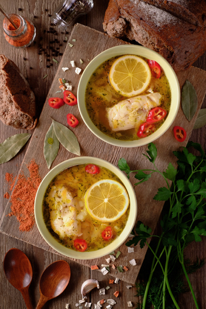 Fish soup with lemon, vegetables and spices on the table