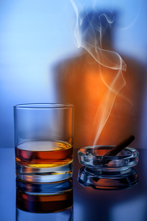 Whiskey in a glass with a cigar and smoke in the form of background