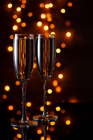 Two wine glasses with champagne on the background of lights