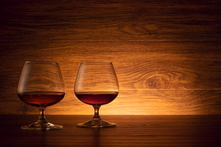 The two brandy glasses on a wooden background. Cognac on the table