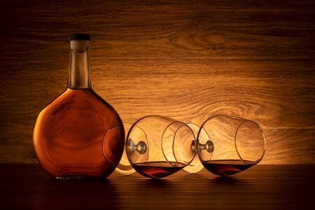 A bottle of cognac and two wine glasses on the table. Brandy on wooden background