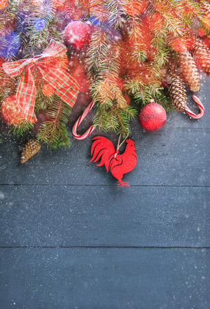 caroler: Christmas background with decorations. New Year 2017 symbol - Fire Rooster. Gifts in craft paper, pine cones, red hearts and confetti. Flay lay, top view. Stock Photo