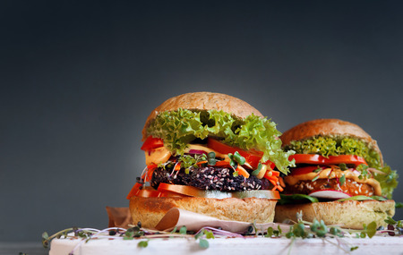 red quinoa: Two mouth-watering and delicious vegetarian burger on a black wooden background. veganburger. the concept of healthy and wholesome food. with microgreen.