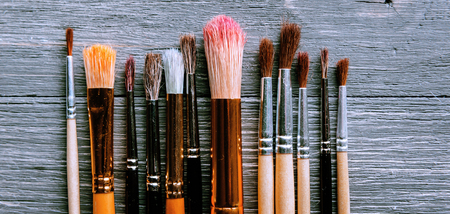 Row of artist paintbrushes closeup on artistic background.
