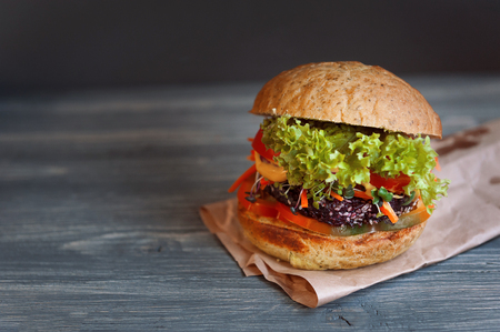 wholesome: fresh and tasty veggie burger on a black wooden background. veganburger. the concept of healthy and wholesome food. with microgreen. Stock Photo