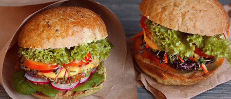 Two mouth-watering and delicious vegetarian burger on a black wooden background. veganburger. the concept of healthy and wholesome food. with microgreen.
