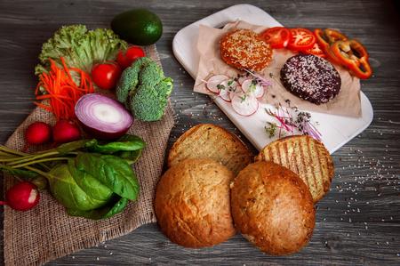 Vegetables and bread rolls for a vegetarian burger on a black wooden background. veganburger