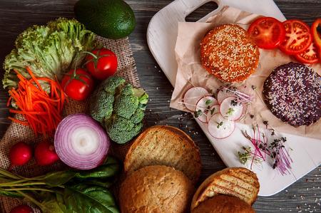 school cafeteria: Vegetables and bread rolls for a vegetarian burger on a black wooden background. veganburger