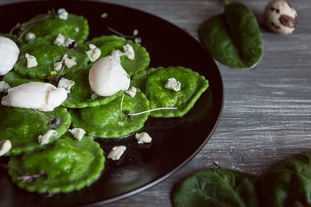delicious green ravioli with the addition of spinach dough, stuffed with ricotta and porcini mushrooms. poached quail egg, blue cheese. on a black plate on a wooden background.