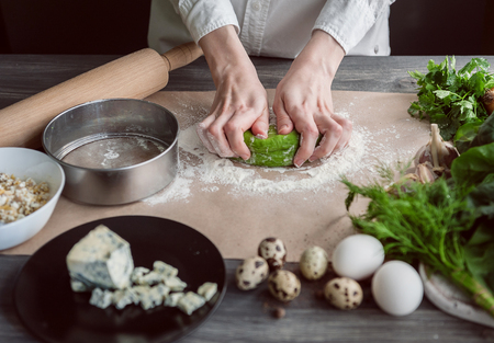 woman kneads dough for ravioli with spinach adding to the dough, stuffed with porcini mushrooms and ricotta. with quail eggs poached. on a dark background.