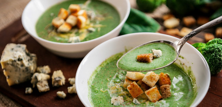Green cream soup of spinach and broccoli. with the addition of parmesan and blue cheese with croutons. a wooden background. kontseptsiyach healthy diet.