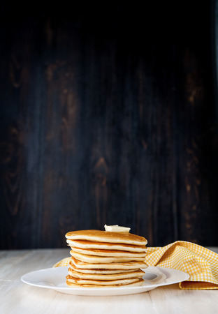 Pancake on a white plate with a piece of butter on a wooden background Stock Photo