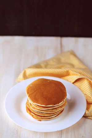 Pancake on a white plate on a wooden background Stock Photo