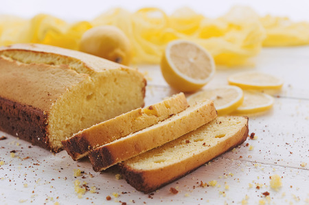 lemon cake with fruits on white wooden surface Standard-Bild