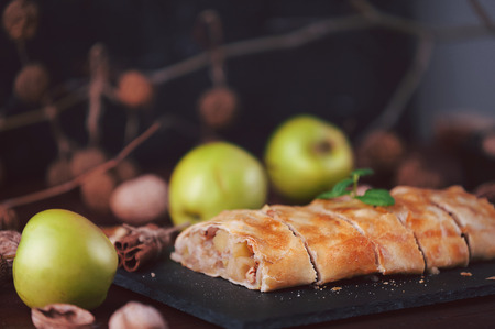 strudel with apples, raisins and walnuts in rustic style on a dark background