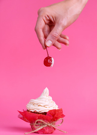girl takes cherry from the cake spread with cream. the concept of sexual pleasures. pink background, studio shooting Stock Photo