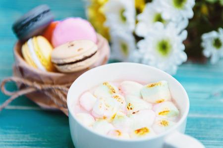 Macarons and mug with hot chocolate and marshmallows