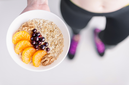 Oatmeal with fruit berries and cereals in the hands of a sportswoman