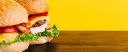 Heldere sappige smakelijke hamburgers met chops, kaas, gemarineerde komkommers, tomaten en spek