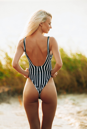 Shapely athletic healthy girl with a beautiful body and elastic buttocks on the beach Stock Photo